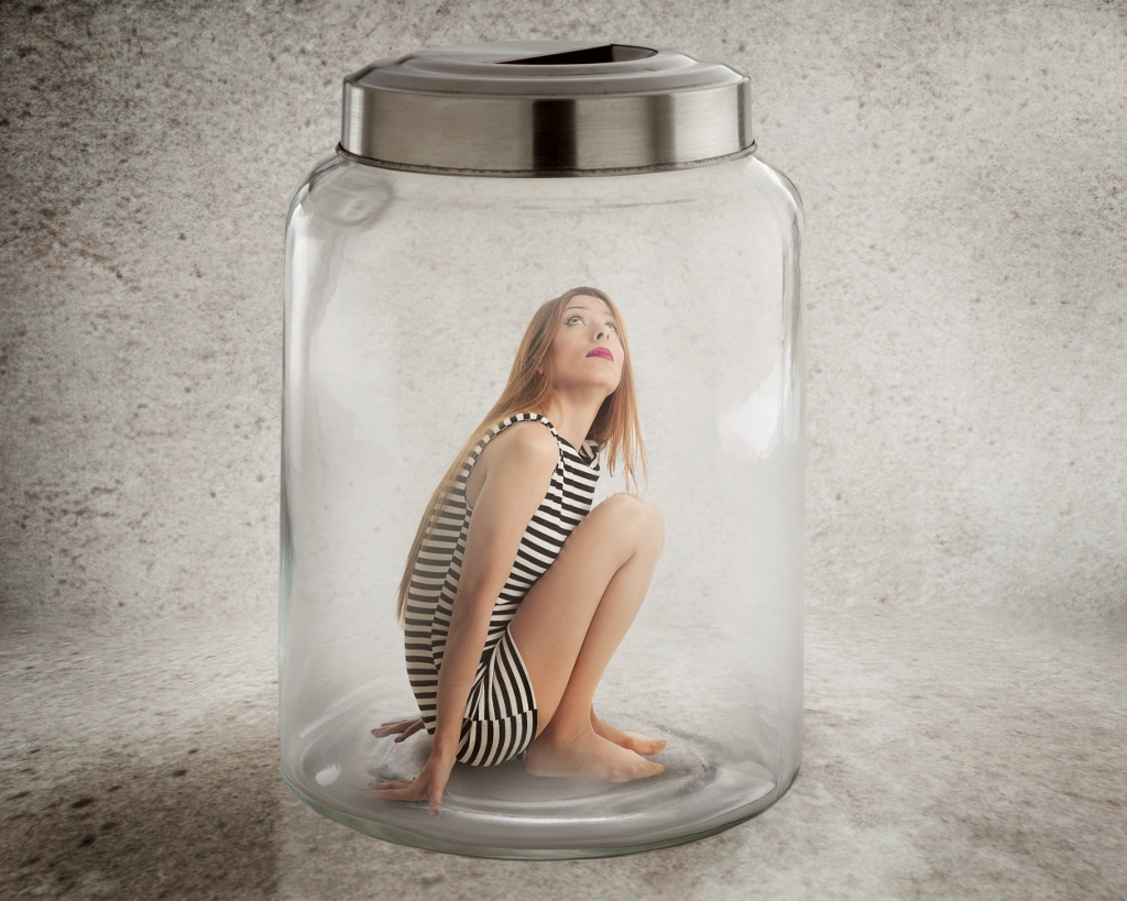 Young lonely woman sitting in glass jar
