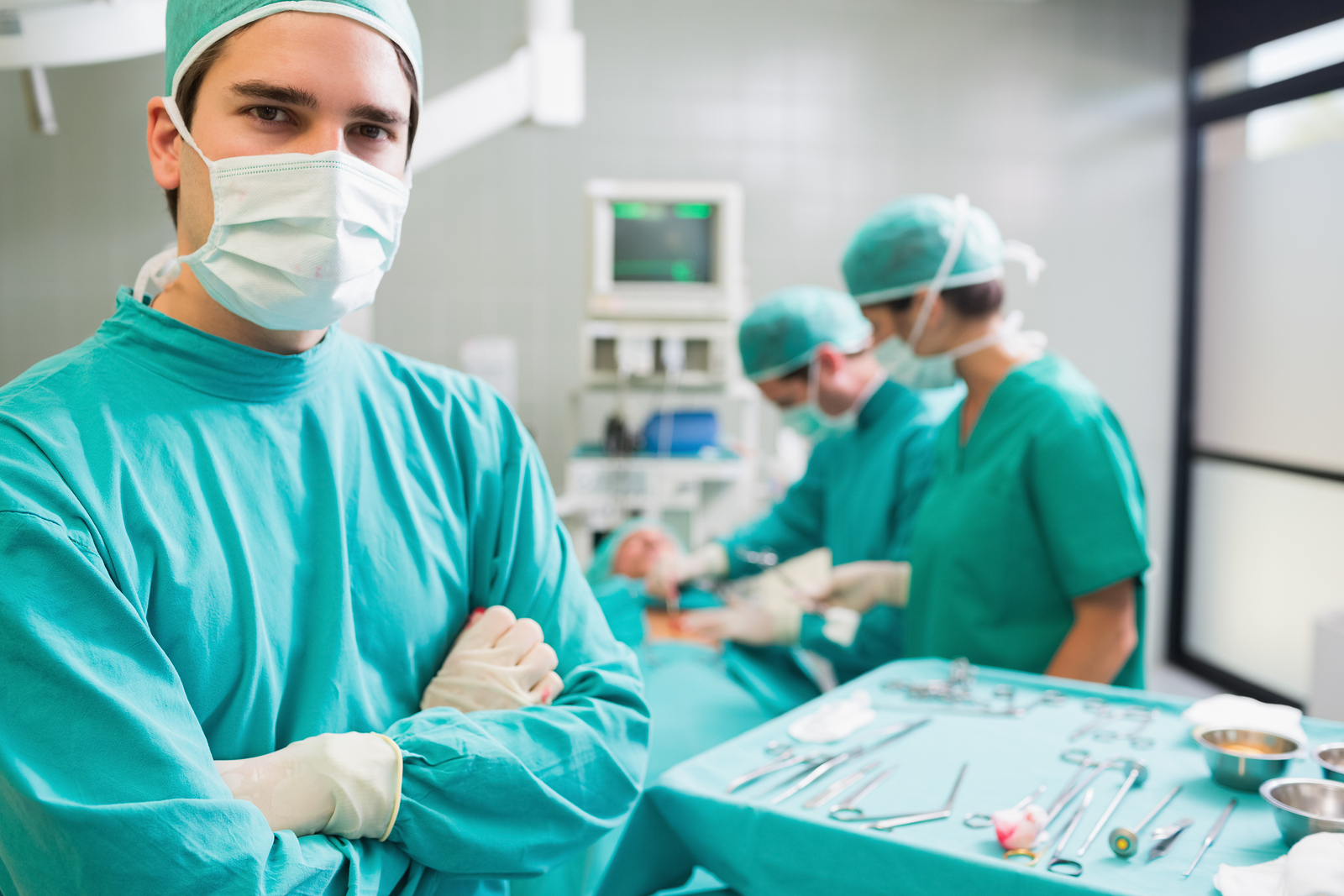 Surgeon with arms crossed looking at camera with colleagues perf
